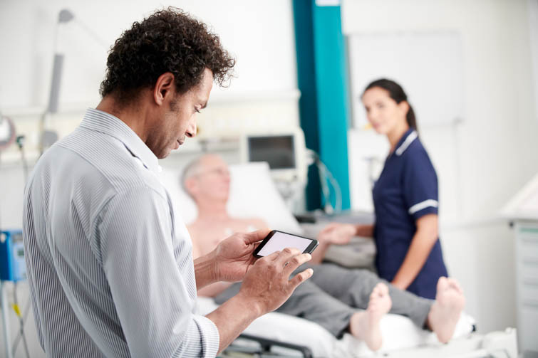 Clinician holding mobile device on hospital ward