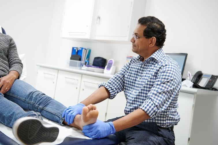 Orthopedic Consultant examining patients foot