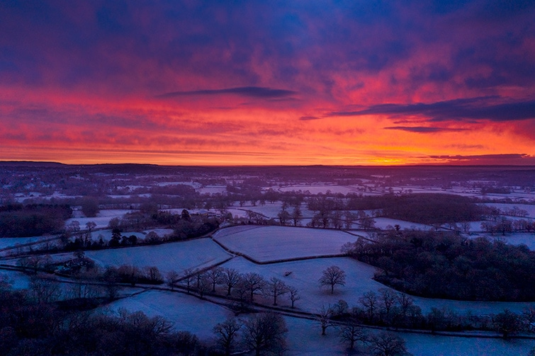Aerial drone sunrise landscape over surrey fields