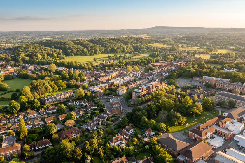 Drone view of Reigate Town Centre and Priory Park during sunset with Reigate High Street, Priory Park, Bell Street, Reigate Castle, Reigate Hill.