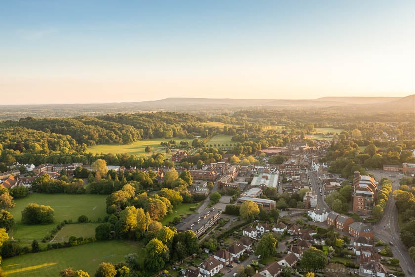 Drone view of Reigate Town Centre and Priory Park during sunset.